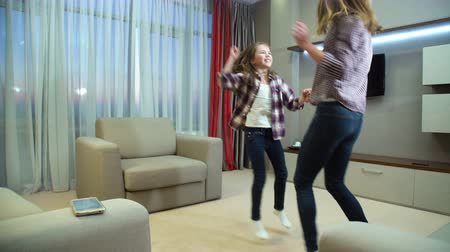 happy family active leisure. loving relationship. music lifestyle. childhood crazy joyful moments with parent. mom and daughter have fun dancing to their favourite song