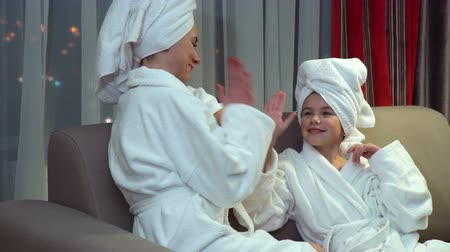 family leisure. mother and daughter communication teamwork. high five. after bath pastime. talking before bedtime