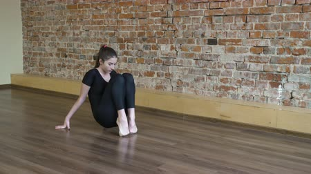 sport fitness. yoga gymnastics. workout training. young fit teenage girl warming up and stretching toes in a gym