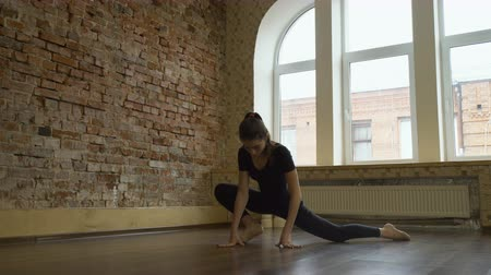 sport fitness. gymnast training routine. flexibility workout. young fit focused teenage girl stretching in a studio