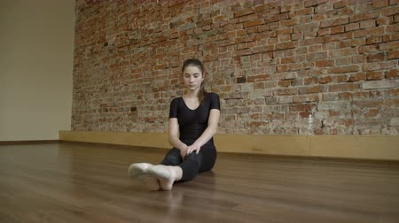 sport fitness lifestyle. gymnast training routine. flexibility workout. young fit focused teenage girl stretching in a studio