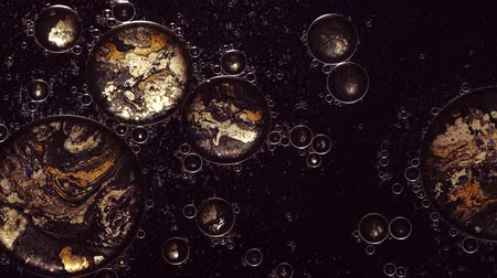 Ink water flow. Abstract fantastic universe. Golden bubbles. Dark glitter paint motion.