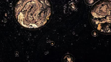 shimmer : Ink water flow. Galaxy planets. Golden bubbles. Black shimmering paint motion.