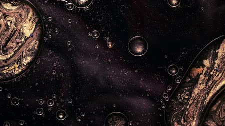 солнечный : Ink water flow. Cell fission effect. Black glitter paint motion. Golden bubbles.