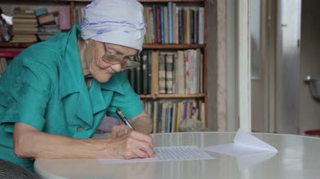 escrever : old woman writing letter then take off glasses