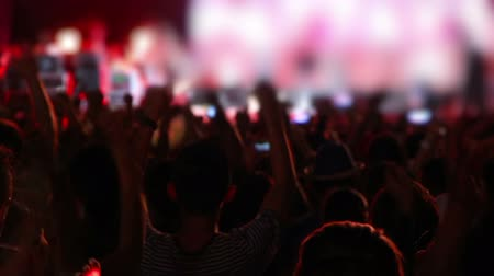 rock concert : big crowd of people raising hands up at rock concert