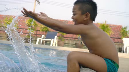 plavání : Little boy sits near swimming pool and plays with water slowmotion