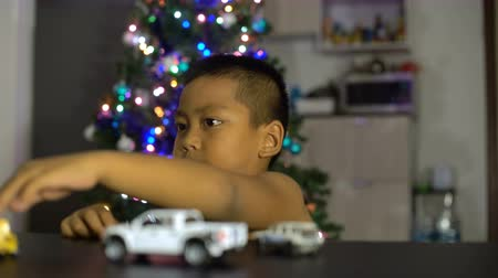 подарок : Little asian boy having fun with gift toy cars. Christmas lights on background 4k (3840x2160)