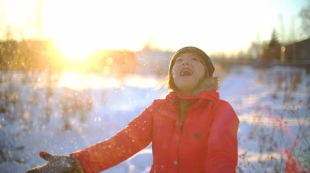 maska : Young Woman throwing snow at sunset. Slowmotion filmed at 120p Wideo