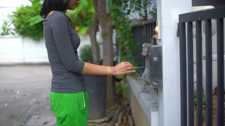 skrzynka pocztowa : Young Asian woman getting electricity bill from post box 4k UHD 3840x2160