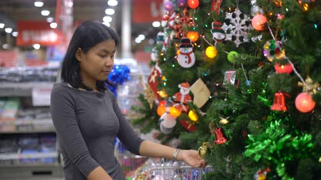 angrily : Woman is touching christmas tree decorations in supermarket 4k UHD 3840x2160 Stock Footage