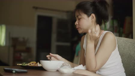 greedily : Young Asian Woman eats greedily in living room