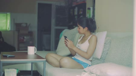chill out : Young Thai Woman is taking selfie while sitting on sofa. Slow motion