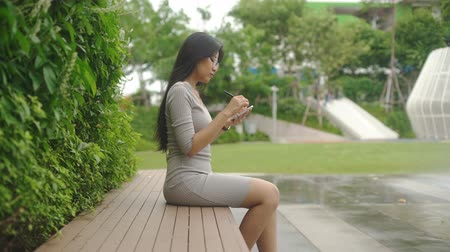 ilustrador : Young Asian Female graphic designer is sketching in park. Slow motion