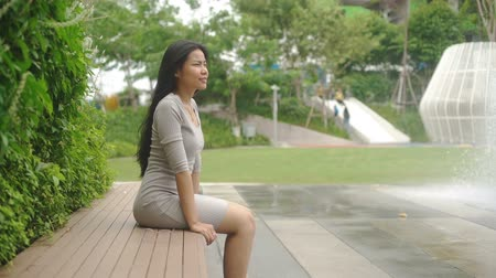 benches : Smiling Young Asian Woman is sitting on bench in park. Slow motion
