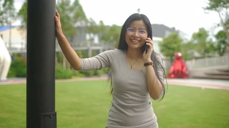 beyaz yakalı işçi : Happy Young Asian woman in glasses is talking on phone. Slow motion