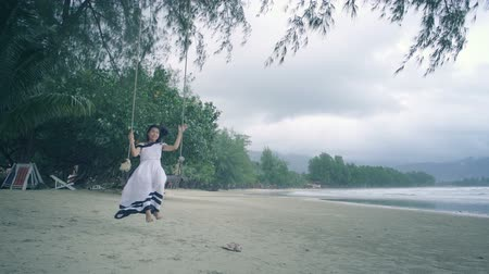 monção : Girl in white dress swinging on a swing at beach. Clean version. Slow motion Vídeos