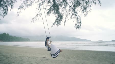 monção : Young Woman in white dress swinging on a swing at beach. Slow motion
