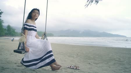 monção : Young Woman in white dress sitting on a swing at beach. Slow motion