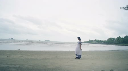 monção : Young Woman in white dress walking at beach. Slow motion