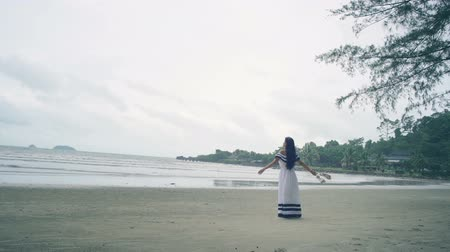 monção : Thai Girl in white dress enjoying of breeze at beach. Slow motion