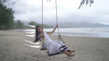 monção : Asian Woman in white dress swinging with drawn traces. Slow motion