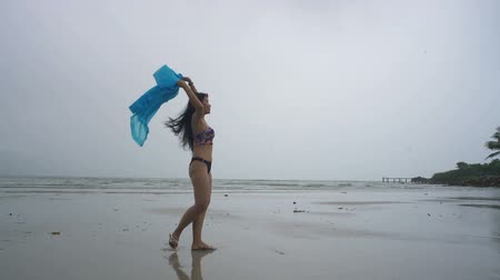 tekmeleme : Asian Girl in bikini and raining coat having fun at beach. Slow motion