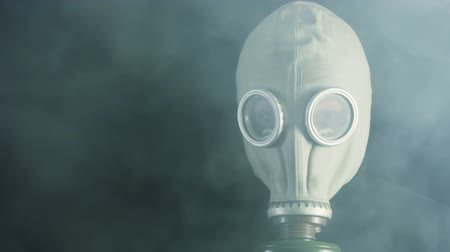gas : Black background. Thick smoke hides man in a gas mask. The smoke dissipated Stock Footage