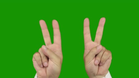 double happiness : Green background (Chroma Key). Mens hands in a white shirt making the hand sign VICTORY. Includes matte for compositing over footage or abstract background Stock Footage