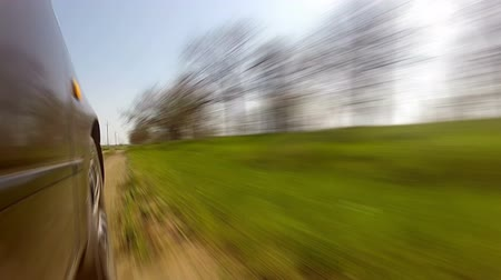 řídit : Spring. The car was going fast down a country road. At first the road in a field, then through the woods. Blue sky. The bright sun