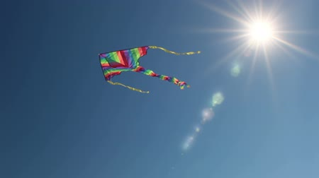 A kite flies against the bright blue cloudless sky. The sun is shining brightly. The glare from the sun