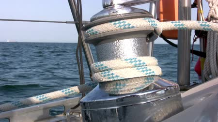 winch : Men rotates the yacht winch and pull the halyard against the backdrop of blue sea and blue sky. Winch sparkles in the sun