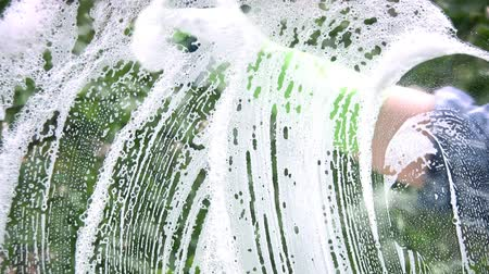 mosás : Womens gloved hand soap washes off the glass and soap on a background of bright green trees Stock mozgókép