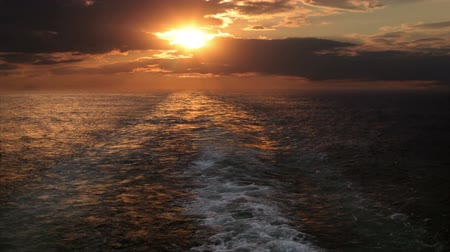 uyanmak : View from the stern of a cruise ship on the multicolored sunset on a cloudy sky. Wake of the ship. Boundless ocean Stok Video