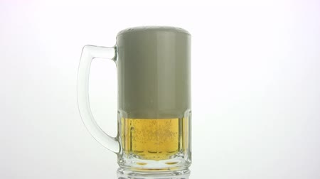 pint glass : The beer by a jet is poured in a mug, the bubbles rise to a surface. A white background