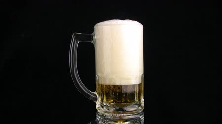 içme : The beer by a jet is poured in mug. beer foam is poured through edge of mug, and in a mag - sits. A black background Stok Video