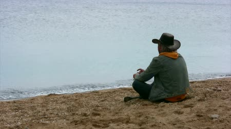 tramp : Wistful cowboy sits on a sandy beach and threw stones into the water