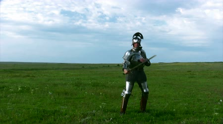 rytíř : Medieval knight in armor, and with an open visor exercise with a sword against the backdrop of steppe grass and blue sky