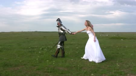 şövalye : Man in medieval armor is excellent for hand girl in a white wedding dress on the boundless steppes