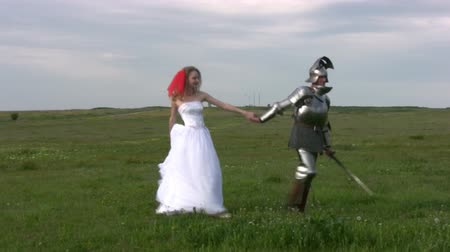 rycerz : Man in medieval armor is excellent for hand girl in a white wedding dress on the boundless steppes