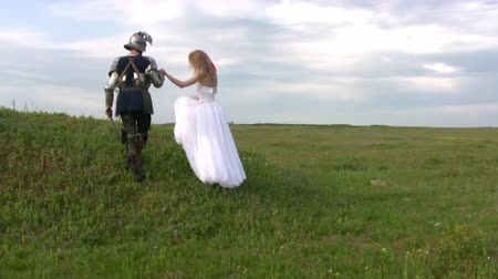 средневековый : Man in the outfit of medieval warriors and an open visor helps the girl, dressed in a white wedding dress up the hill on a background of endless steppes and overcast sky Стоковые видеозаписи
