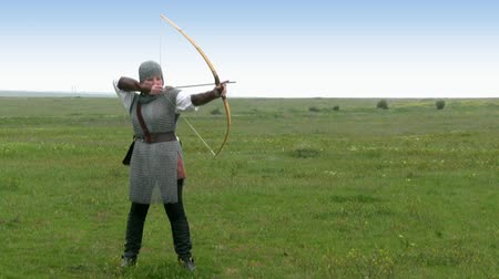 strzałki : Girl in a vestment of medieval warrior takes an arrow from the quiver and shoots from a bow on a background of endless steppes, and the clean sky Wideo