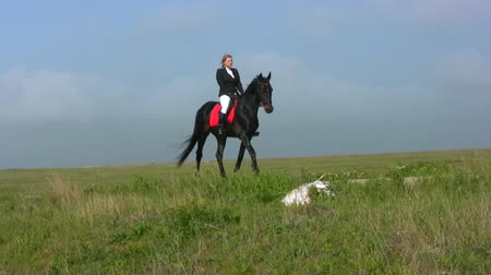 horse riding : Equestrienne wearing jockeys approaching on the road against the backdrop of the steppe green grass and blue sky