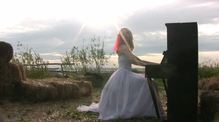fortepian : Bride in wedding dress plays the piano, which stands in the steppe on the background of bales of hay and the sunset. Evening. The back light