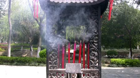 myrrh : Sunny weather in a Chinese park. Incense smoke in the old national stand Stock Footage