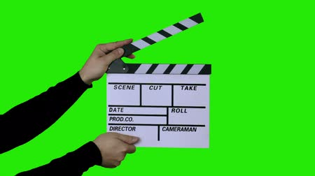 confecção : 3 in 1 (small, medium and large distance). Mens hands in a black sweater are clapping film clapboard (film slate) on green chroma key