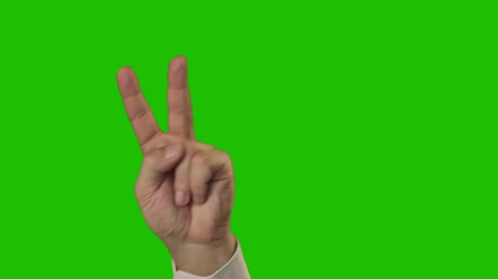 sembol : Green background (Chroma Key). Mens hands in a white shirt making the hand sign VICTORY (11 times) Stok Video