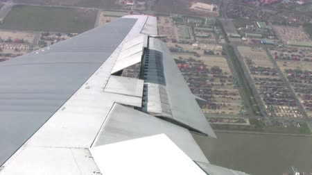 szárny : View from the airplane on the industrial area of the city. The plane makes a turn before landing. Smog hangs over the city