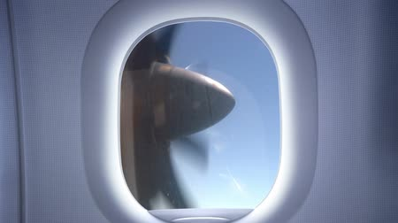 airplane engine : The view from the window of a small plane on a clear blue sky. Its sunny. Shown to the propeller blades which rotate rapidly Stock Footage
