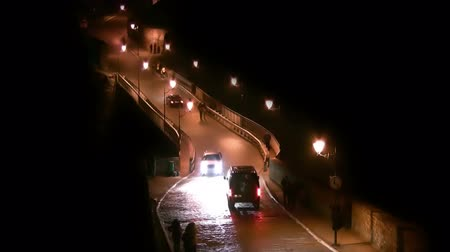 macskaköves : Night. People and cars going through the old cobbled bridge lit by old street lamps Stock mozgókép
